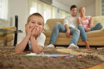 Familia viendo TV en piso de alquiler