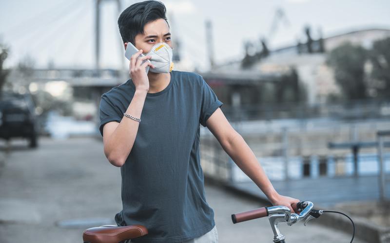 chico en bici con mascarilla