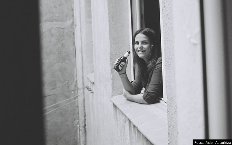 Chica bebiendo asomada a una ventana de Madrid
